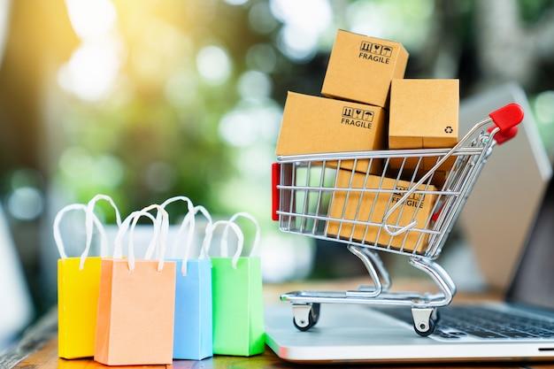 Winkelen online concept met kar, tassen, pakket dozen en laptop op tafel met kopie ruimte