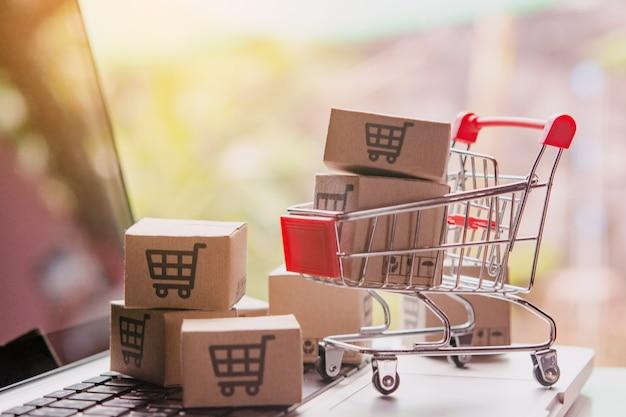 Winkelen online concept - pakjes of papieren dozen met een winkelwagentje in een trolley op een laptoptoetsenbord. boodschappenservice op het online web. biedt bezorging aan huis.