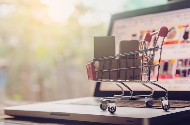 Winkelen online concept. pakket- of papierdozen met een winkelwagenlogo in een trolley op laptoptoetsenbord. boodschappenservice op het online web. biedt levering aan huis.