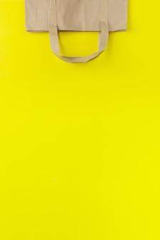 Winkelen papieren zak op de gele achtergrond met kopie ruimte. platliggende foto van een omgekeerde tas.
