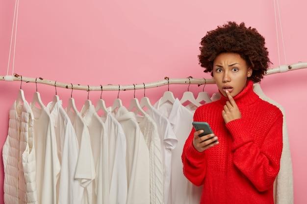 Winkelen, technologie en mensen concept. nerveus krullend vrouwelijke stylist vormt in de buurt van veel witte kleren op rekken, draagt een rode gebreide trui, maakt gebruik van mobiele telefoon,