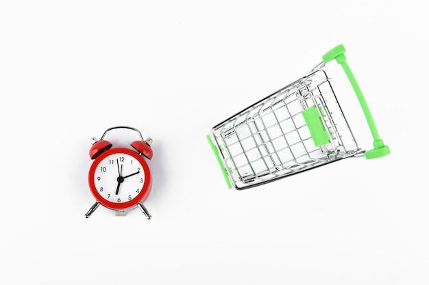 Winkelen tijd concept. online winkelen concept. kar en rode retro wekker op wit