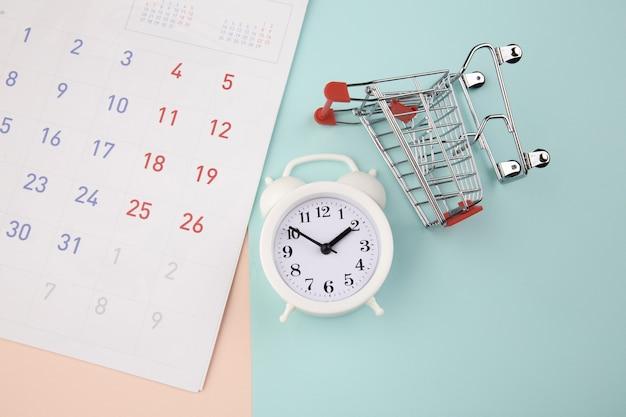 Winkelen tijd concept. supermarktwagen met wekker en kalender. bovenaanzicht.