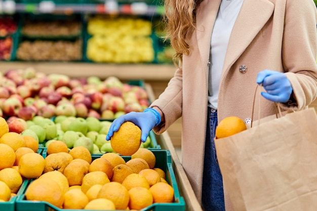 Winkelen tijdens de coronavirus covid-19 pandemie. vrouw in gezichtsmasker en rubberen handschoenen koopt citrusvruchten op de markt.