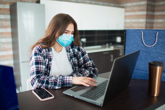 Winkelen tijdens quarantaine. een vrouw zit achter een laptop en koopt goederen op het internet in een masker. winkelen ten tijde van de pandemie van het coronavirus