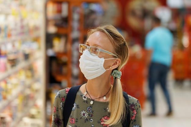 Winkelen tijdens quarantainevrouw die beschermend gezichtsmasker draagt. levensstijl.