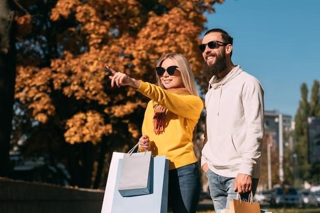 Winkelen toerisme echtpaar wandelen met pakketten in het stadscentrum