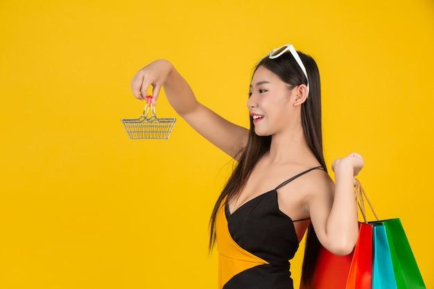 Winkelen van mooie vrouwen die gestreepte overhemden op geel dragen.