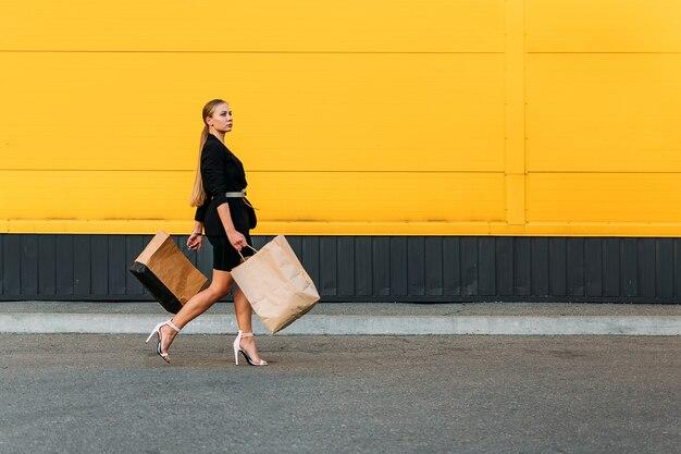 Winkelen, verkoop concept. stijlvolle modieuze vrouw lopen achtergrond