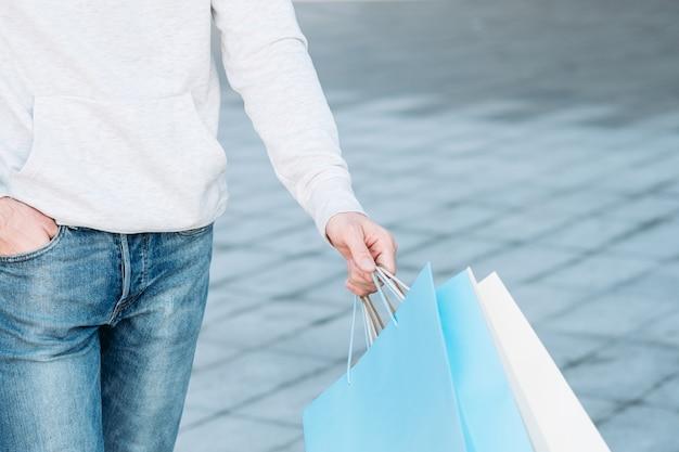 Winkelen vrijetijdsbesteding winkelverkoop casual man met papieren zakken