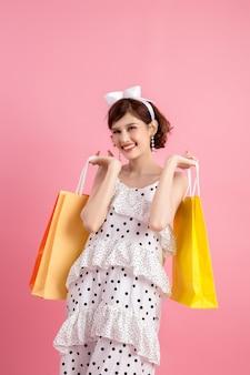 Winkelen vrouw met boodschappentassen op roze