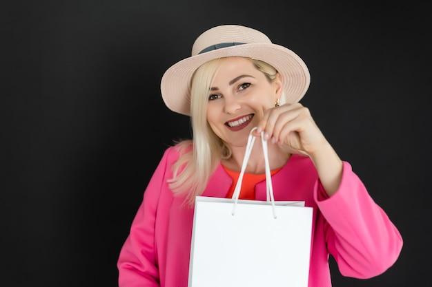 Winkelen vrouw met tassen, geïsoleerd op zwarte achtergrond.