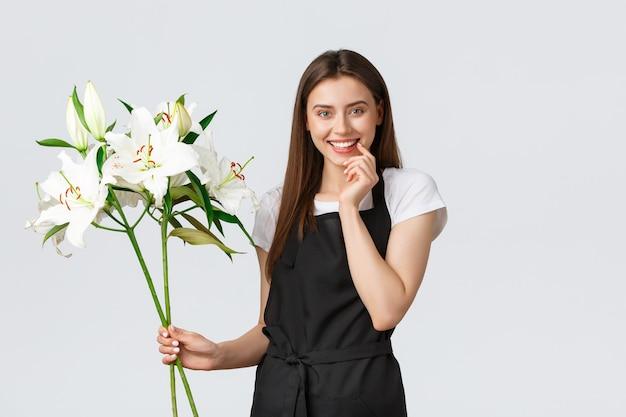 Winkelen, werknemers en klein bedrijfsconcept. glimlachende aantrekkelijke verkoopster in bloemenwinkel die schort draagt, er gelukkig uitziet als het maken van een boeket van witte lelies, staande op een witte achtergrond