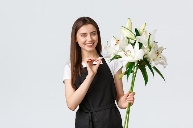 Winkelen, werknemers en klein bedrijfsconcept. glimlachende mooie verkoopsterbloemist in bloemenwinkel die een boeket van witte lelies vasthoudt en glimlacht, maak de bestelling klaar voor de klant