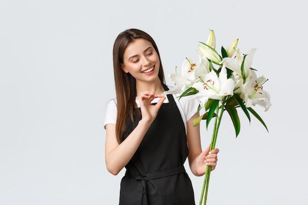 Winkelen, werknemers en klein bedrijfsconcept. glimlachende schattige bloemenwinkeleigenaar in zwarte schort met winkel, bereid een mooi boeket witte lelies voor online bestelling van de klant, witte achtergrond
