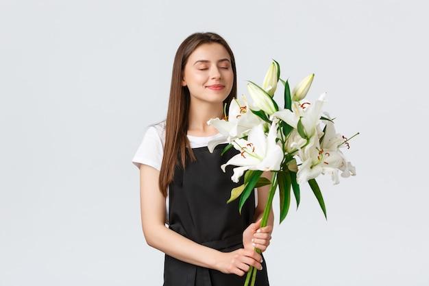 Winkelen, werknemers en klein bedrijfsconcept. lachende dromerige vrouwelijke bloemist in bloemenwinkel sluit de ogen en snuift een lekkere geur van witte lelies boeket, witte achtergrond.