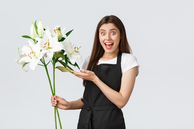 Winkelen, werknemers en klein bedrijfsconcept. opgewonden glimlachende vrouwelijke bloemist in zwarte schort die verbaasd kijkt als een boeket van mooie witte lelies, staande op een witte achtergrond.