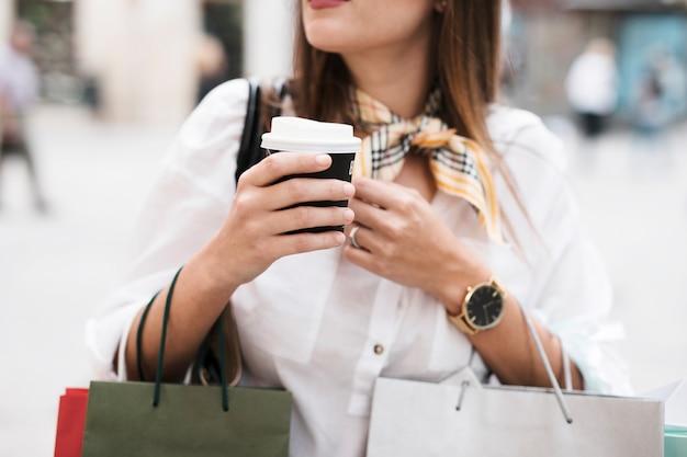 Winkelend meisje dat een koffie heeft
