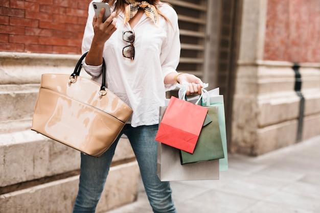 Winkelend meisje dat haar mobiele telefoon bekijkt