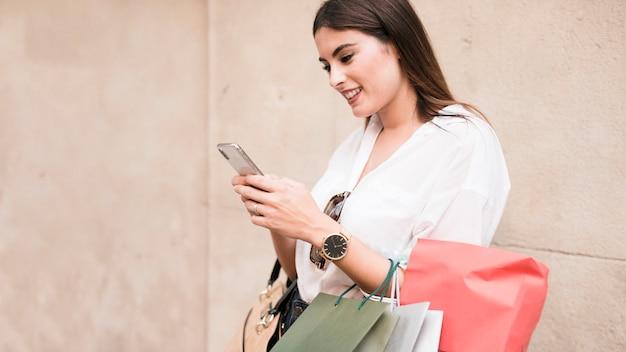 Winkelend meisje dat haar mobiele telefoon met behulp van