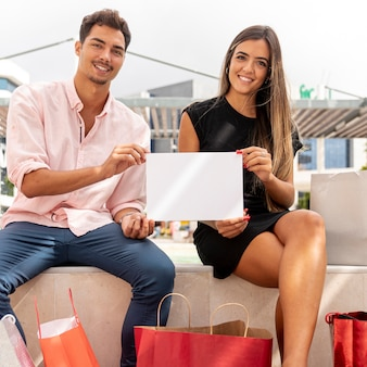 Winkelend paar dat leeg kaartmodel houdt
