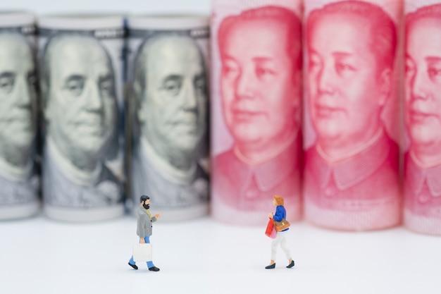Winkelende miniatuurcijfers met amerikaanse dollar en china yuan-bankbiljetten.