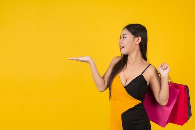 Winkelende mooie vrouw die een kleurrijke document zak op een geel houdt.