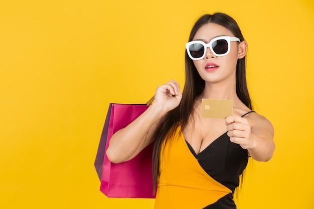 Winkelende mooie vrouw die glazen met een gouden creditcard met een kleurrijke document zak op een geel draagt.