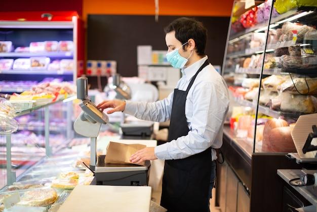 Winkelier lopende zaken terwijl het dragen van masker, coronavirus pandemisch concept