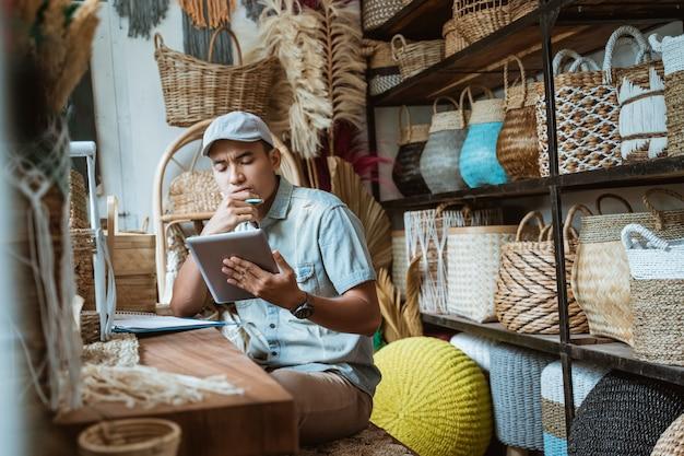 Winkeliers denken na terwijl ze aantekeningen maken met een pen terwijl ze een notitieblok gebruiken in een ambachtswinkel