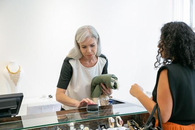 Winkelkassier of verkoper die het betalingsproces uitvoert met een betaalautomaat en een creditcard. klant betaalt voor kleding bij het afrekenen. winkelen of kopen concept