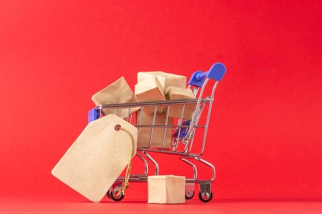 Winkelmandje en dozen met aankopen met plaats om tekst toe te voegen op een rode achtergrond. online winkel- en verkoopconcept