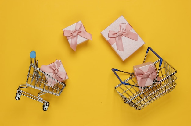 Winkelmandje en karretje, geschenkdoos met bogen op gele achtergrond. samenstelling voor kerst, verjaardag of bruiloft. bovenaanzicht