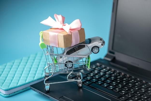 Winkelmandje met auto en geschenkdoos op laptop toetsenbord op blauwe achtergrond