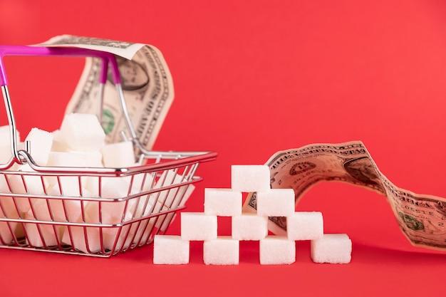 Winkelmandje met suikerklontjes en papiergeldrekeningen op een rode achtergrond. selectieve aandacht. ruimte kopiëren.