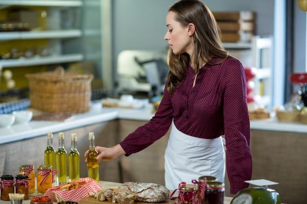 Winkelmedewerker die olijfoliefles bekijken