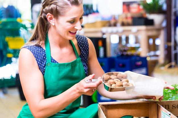 Winkelmedewerkers in hoekwinkel vullen notenzakken