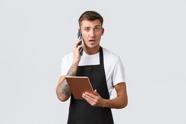 Winkels, kleine bedrijven, café en restaurants afhaalconcept. verward en bezorgd, onzekere verkoper ontvangt een klacht van de klant via de telefoon, kijkt nerveus naar de camera, houdt een digitale tablet vast