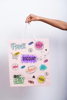 Winkelvoordelen. close-up van vrouwelijke hand met boodschappentas met kleurrijke schetsen erop