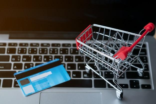 Winkelwagen en cradit-kaart op laptop
