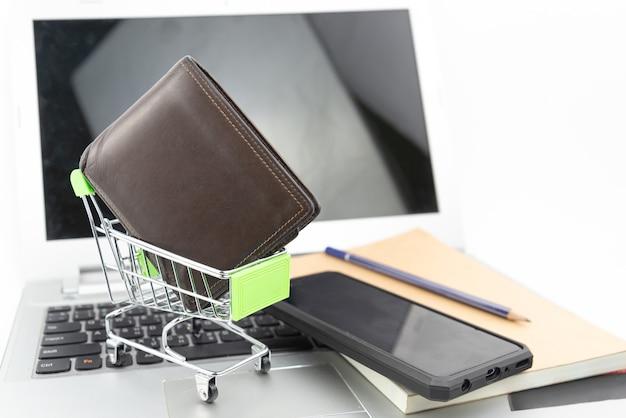Winkelwagen en portemonnee op notebook en laptop achtergrond. online winkelen, investering, aankoop, bedrijfsconcept besparen.