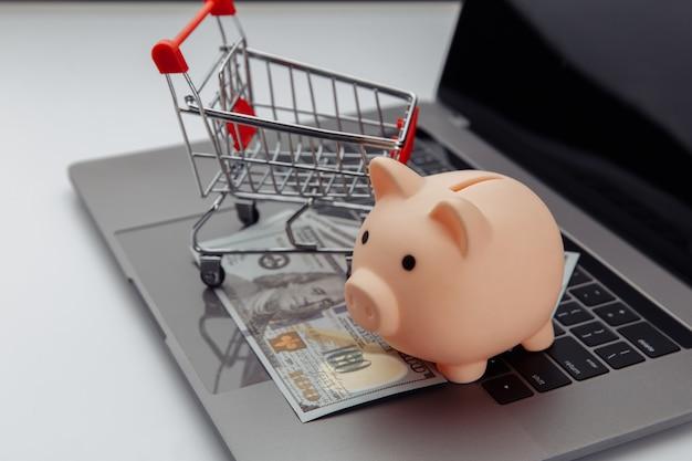 Winkelwagen en roze spaarvarken met laptop op het bureau, online winkelconcept.