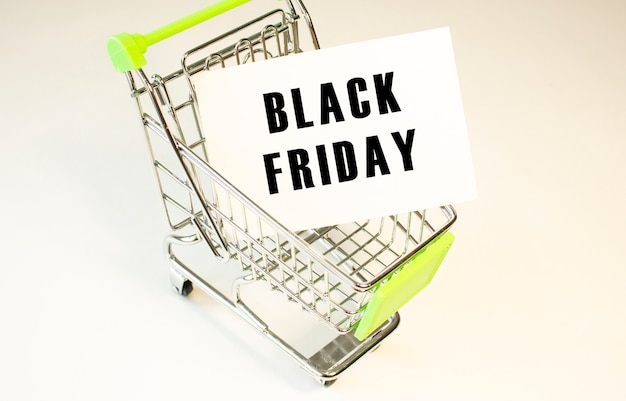 Winkelwagen en tekst black friday op wit papier. boodschappenlijstje concept.