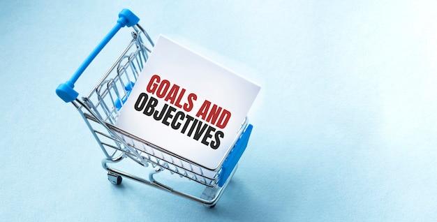 Winkelwagen en tekst doelen en doelstellingen op witboek notitie lijst.