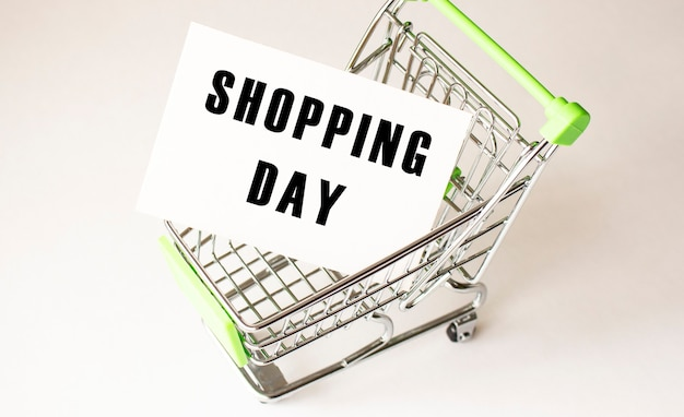 Winkelwagen en tekst shopping day op wit papier. boodschappenlijstje concept op lichte achtergrond.