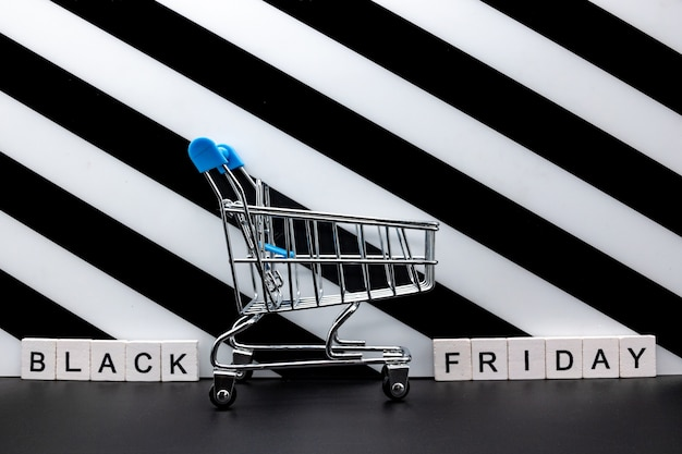 Winkelwagen en zwarte vrijdag tekst op papier scheur