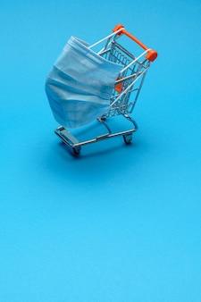 Winkelwagen met coronavirus medisch masker geïsoleerd op een blauwe achtergrond met kopie ruimte.