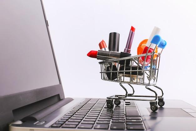 Winkelwagen met cosmetica is op de laptop. online verkoopconcept.