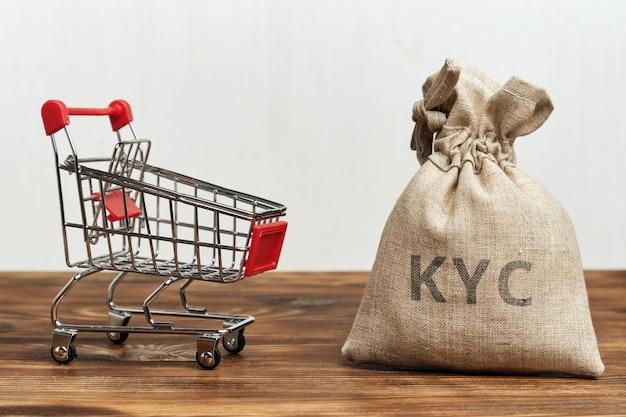 Winkelwagen met een zak geld en een inscriptie kyc.
