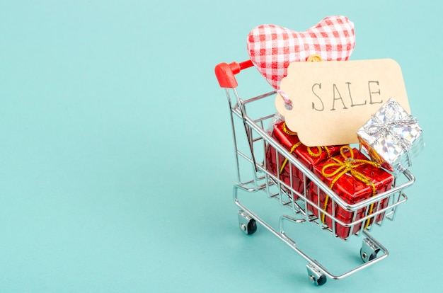 Winkelwagen met geschenkdozen en verkoop-tag op helder oppervlak